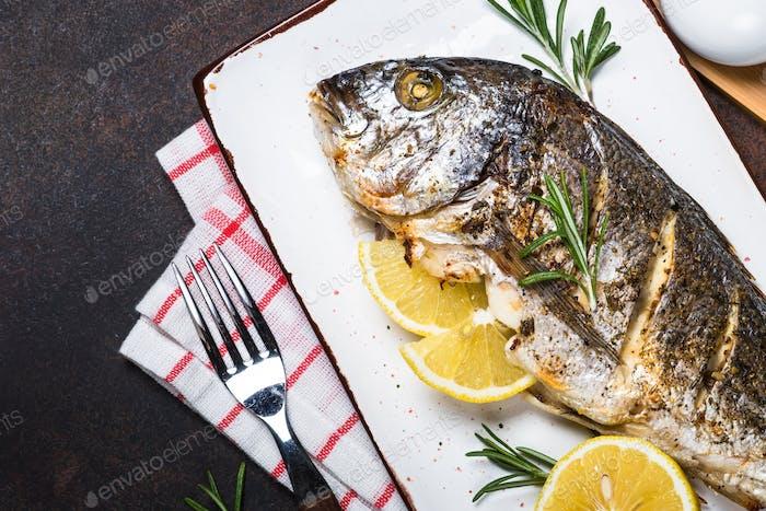 Baked dorado fish with lemon and rosemary.