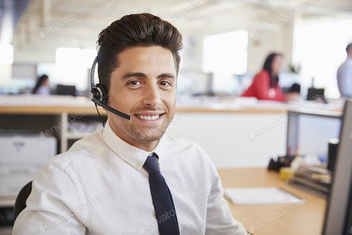 Hispanic male call centre worker smiling to camera, close-up
