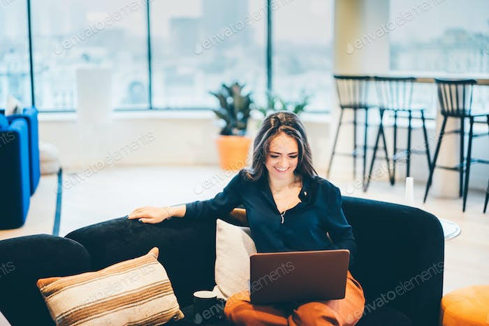 Businesswoman working on laptop in modern coworking.