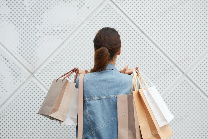 Dame mit Haufen Einkaufstaschen
