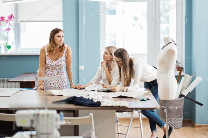 Three smart-looking pretty women are pointing at the sewing magazine. Tailor's dummy is in the