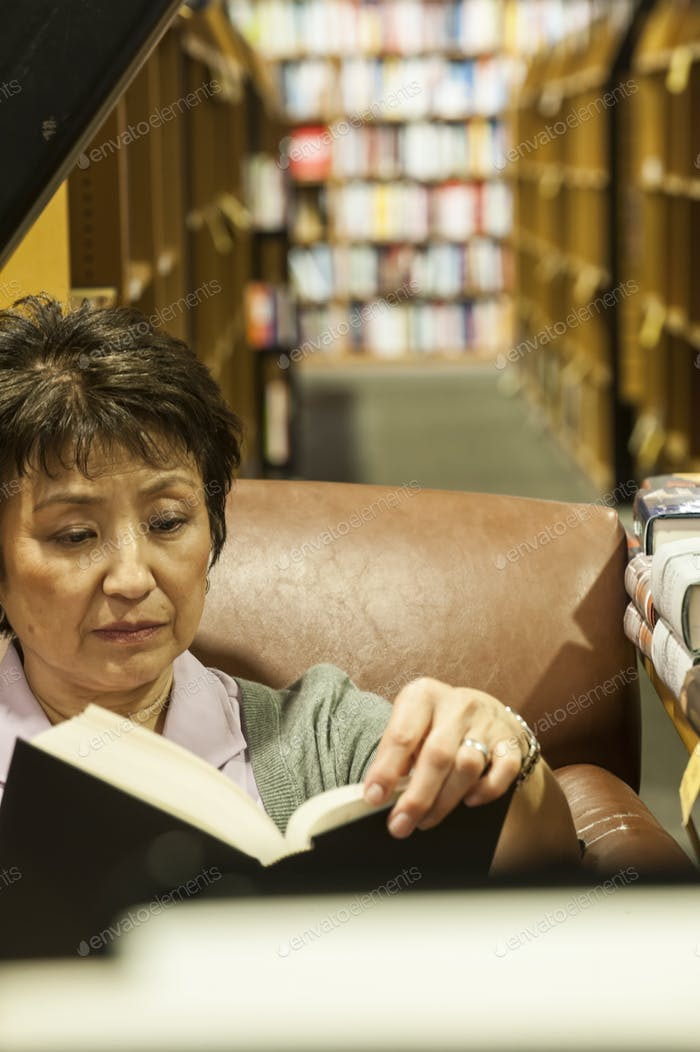 Asian American woman browsing through books in a bookstore