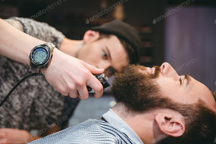 Bearded man getting his beard shaved by modern barber