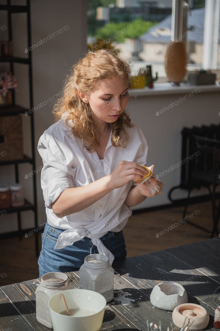 Female potter sitting and stirs paint with a brush a cup on the table. Woman making ceramic item