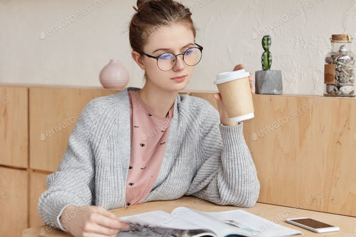 Serious confident young female in glasses looks attentively into magazine, drinks tea, reads interes