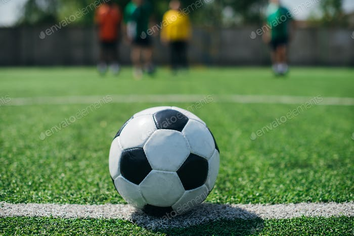 selective focus of football ball and players on green football field
