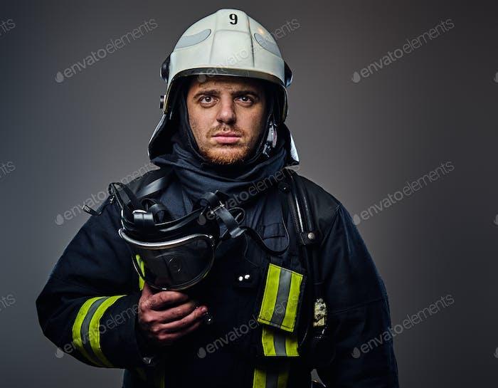 Studio portrait of firefighter dressed in uniform.