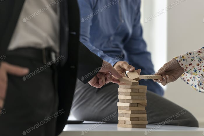Group of colleagues in an office carefully building a tower of w