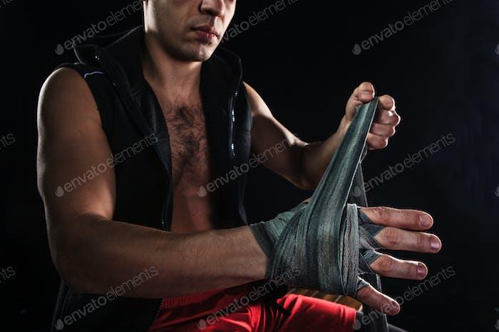 Руки мускулистого человека с повязкой