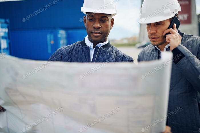 Two engineers reading plans while standing in a shipping yard