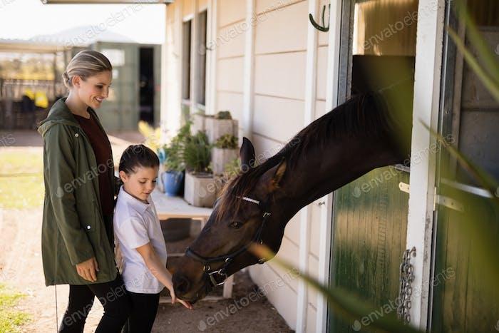 Mutter und Tochter füttern ein Pferd im Stall