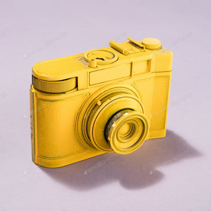 Yellow camera on pastel background.