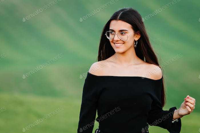 Candid woman with perfect teeth and smile posing at green meadow