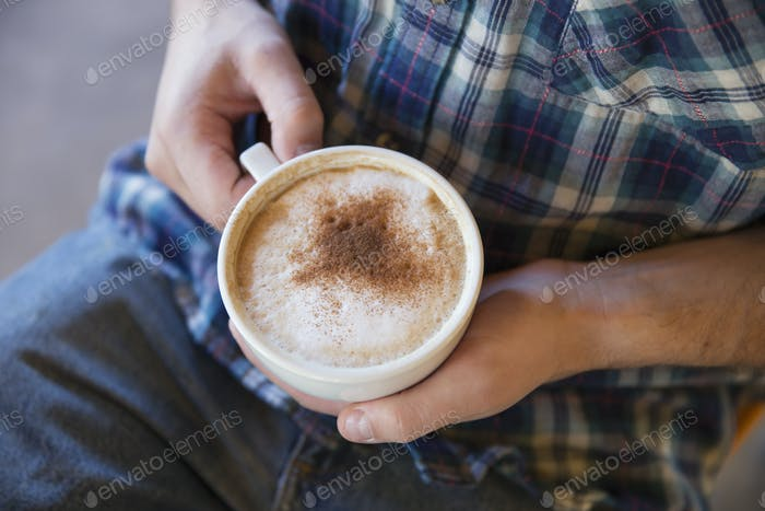 A person holding a cup of coffee in two hands.