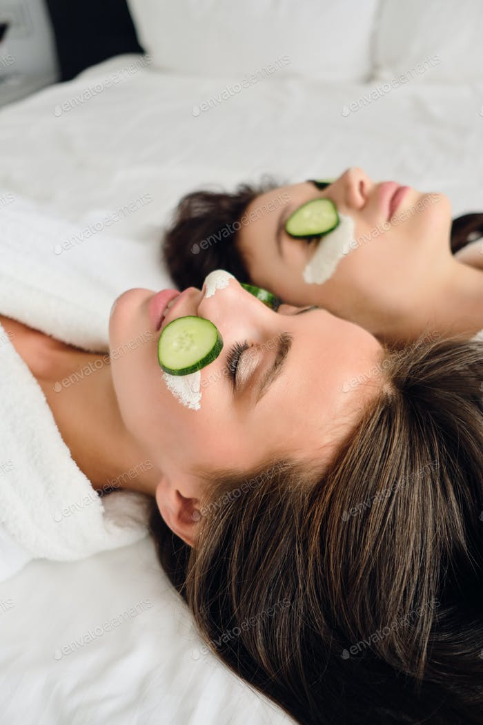 Two young pretty women in white bathrobes with cosmetic mask and slices of cucumber on faces