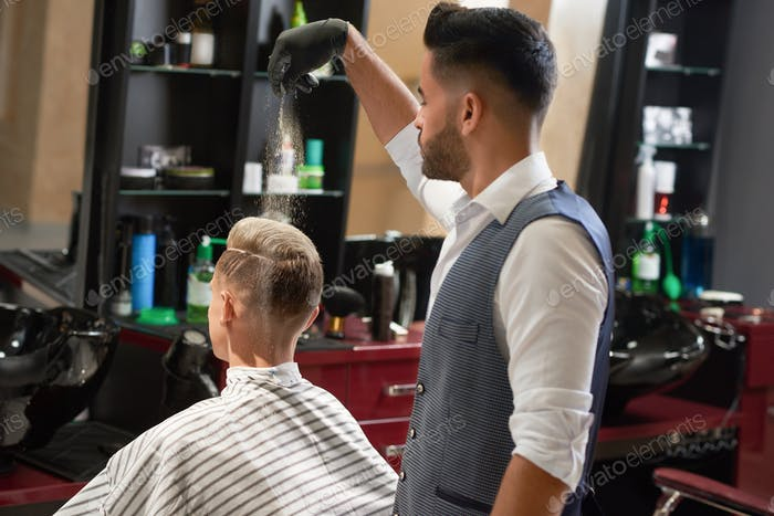 Master in barbershop powdering client for perfect hairstyle