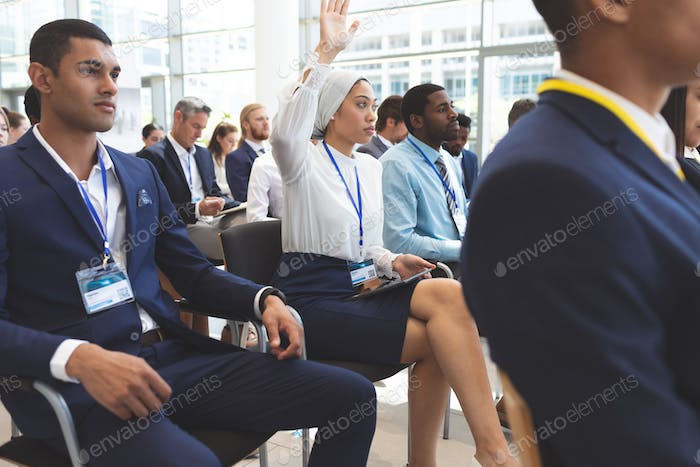 Side view of mixed race businesswoman raising hand in business seminar in office building