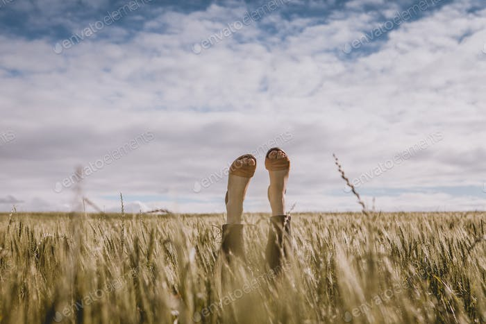 Woman Laying in Field with Feet in the Air