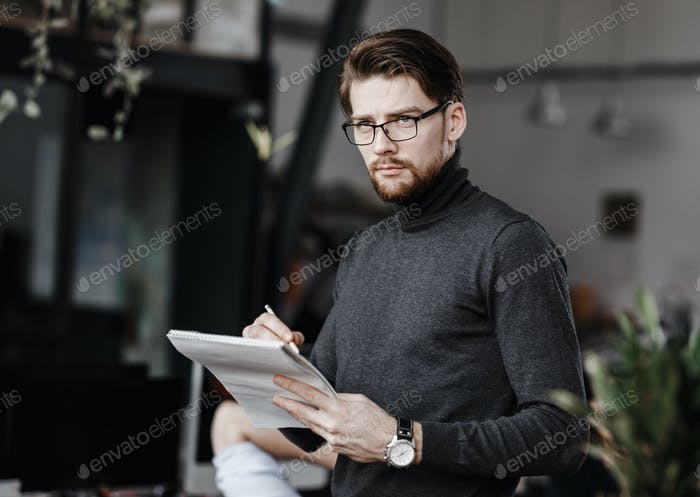 The guy dressed in casual office style clothes makes notes in a notebook in the modern office