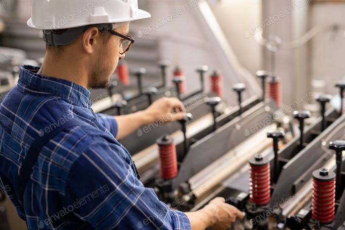 Young engineer standing by industrial machine while operating it in working area