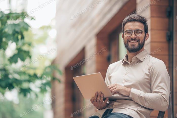Lächelnder Mann mit Laptop im freien