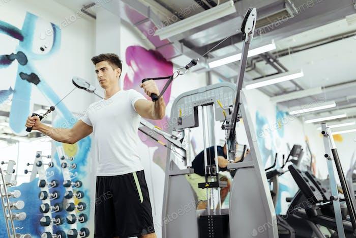 Handsome man training in clean modern gym