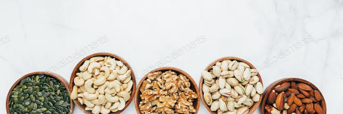 Different kind of nuts in wooden bowls