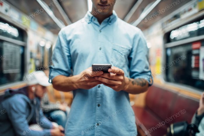 Man using phone in subway car, addicted people
