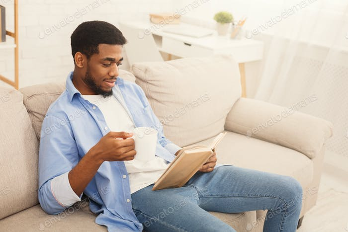 Young african-american man reading book at home