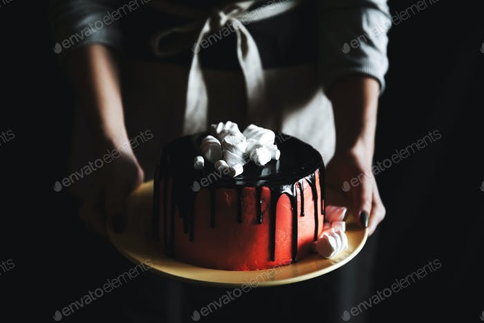 Woman holding cake with marshmallow on black background