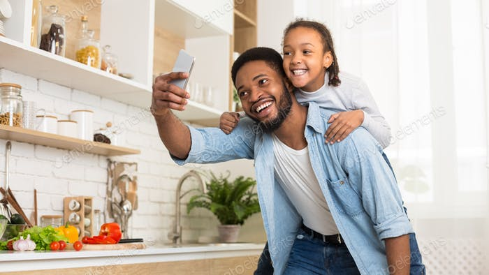 Afro dad and daughter taking selfie on cellphone in kitchen