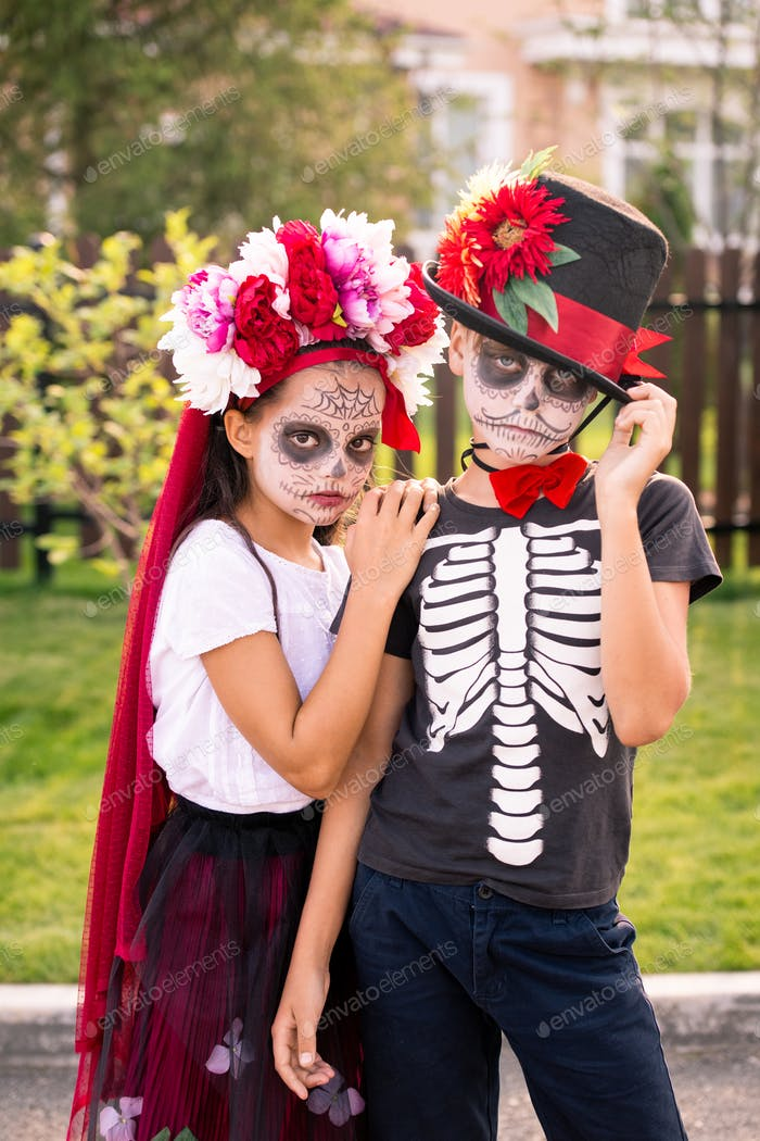 Two gloomy halloween kids with painted faces standing close to one another