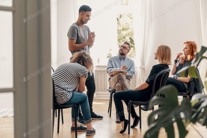 Glücklicher spanischer Mann im Gespräch mit seiner Unterstützungsgruppe über seinen Erfolg