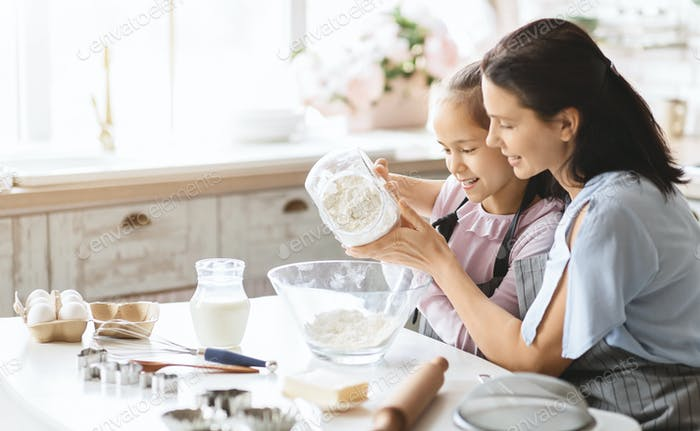 Mother and daughter preparing dough for bake cookies, adding flour to bowl