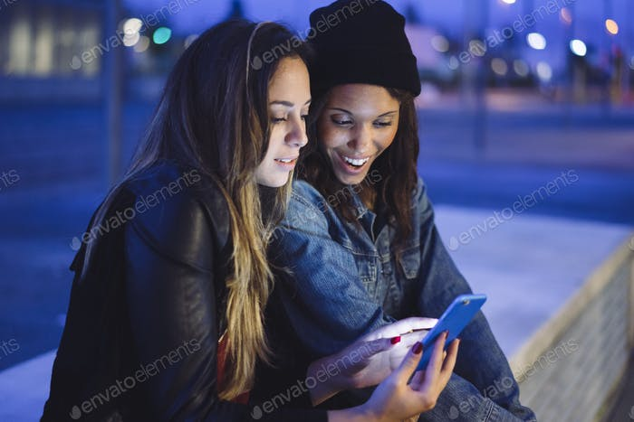 two young female friends chatting and looking at their mobile phone