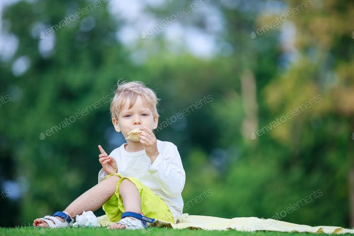 Cute blonde boy eating ice cream in a park