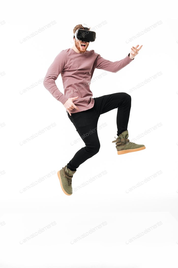Young man in virtual reality glasses jumping and playing like a guitar over white background