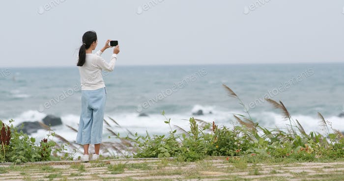 Woman taking photo on cellphone with the sea
