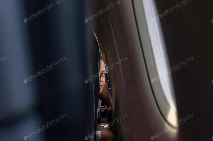 passenger children looking outside of airplane window