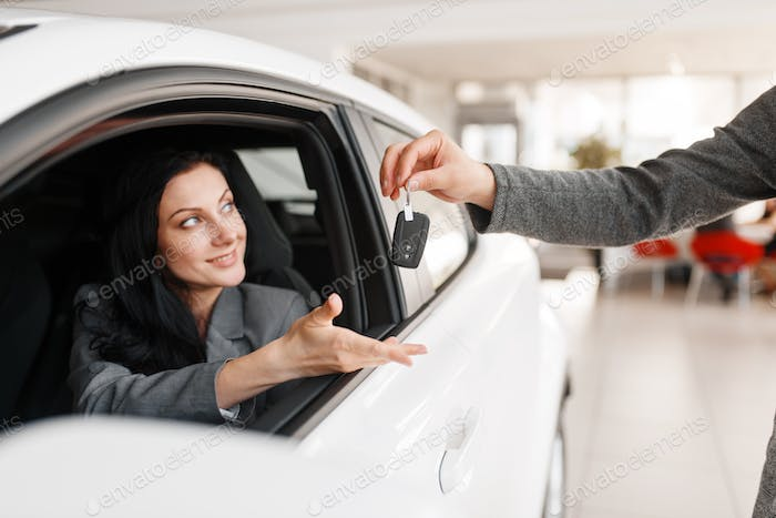 Happy woman takes the key to new car in showroom