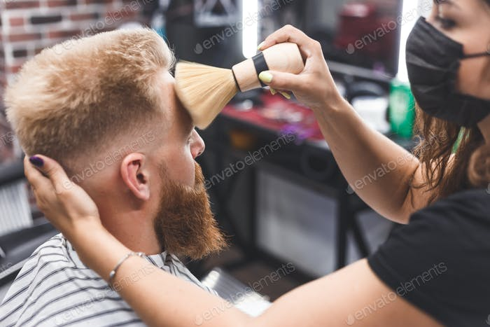 The hairdresser cleans the face of a young guy with a brush after a haircut