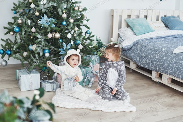 Two little sister girls open their gifts at the Christmas tree in the morning on the deck