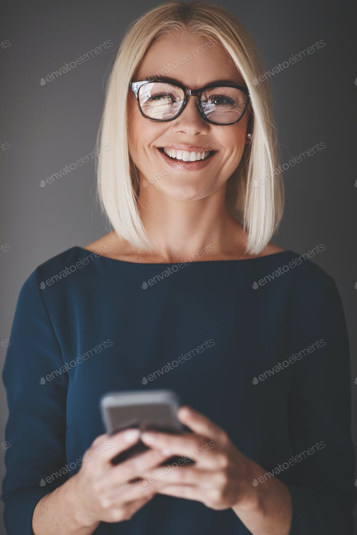Smiling businesswoman using her cellphone against a gray background