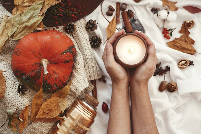 Autumn flat lay. Hygge lifestyle. Pumpkin and candle in hand