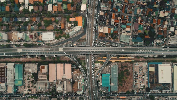 Top down cars drive at cross freeway in aerial view. Highway traffic transportation at Manila city