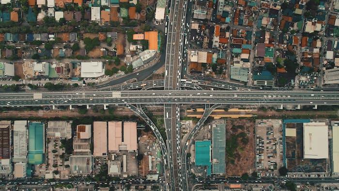 Los  coches de arriba abajo conducen en la autopista cruzada en vista aérea. Transporte de tráfico por carretera en la ciudad de Manila