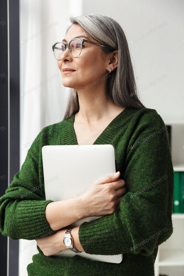 Photo of gray-haired serious businesswoman holding laptop
