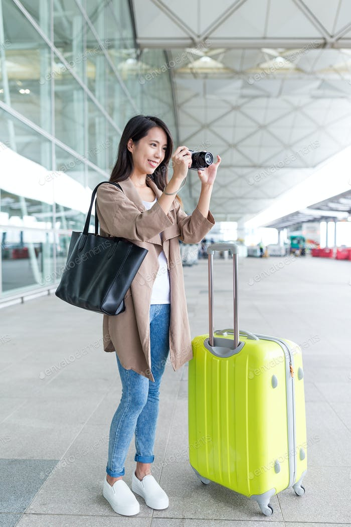 Asian Woman shooting by camera with her luggage in airport