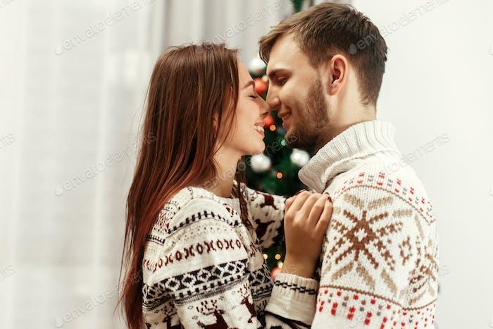 Glückliche Familie sanft umarmt am Weihnachtsbaum