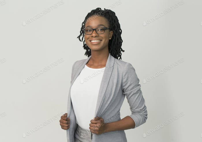 Black Businesswoman Smiling At Camera Standing Over Gray Background